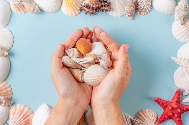 As mãos das mulheres segurar conchas sobre um fundo azul de verão com diferentes conchas e estrelas do mar Foto Premium