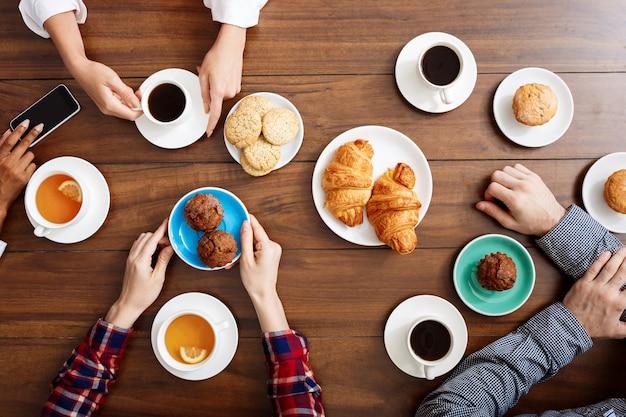 As mãos das pessoas na mesa de madeira com croissants e café. Foto gratuita