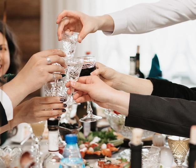 As mãos das pessoas tilintam de copos com bebidas alcoólicas em um feriado em um restaurante Foto Premium