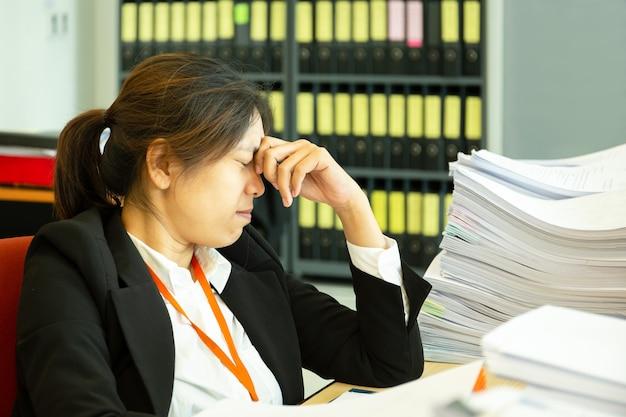 As mãos de descanso da mulher de negócios na cabeça com olhos fecham-se na mesa do trabalho no escritório. Foto Premium