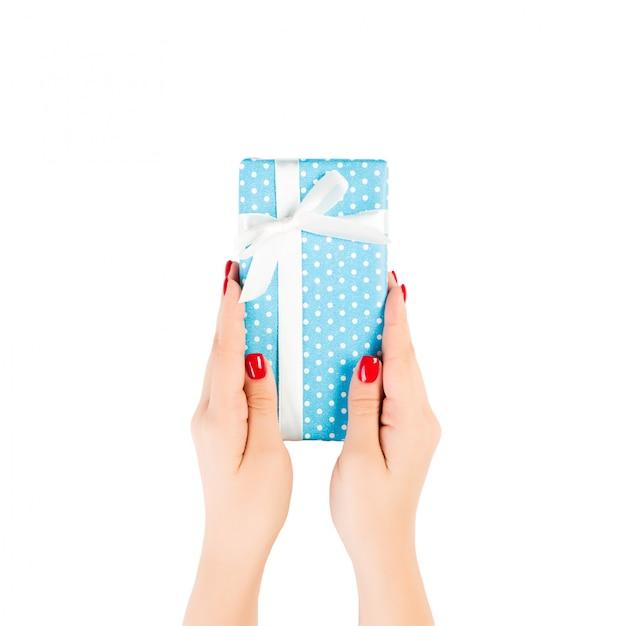 As mãos de mulher dão natal embrulhado ou outro presente artesanal de férias em fita de papel azul e branco. isolado na vista superior, branca. caixa de presente de ação de graças Foto Premium