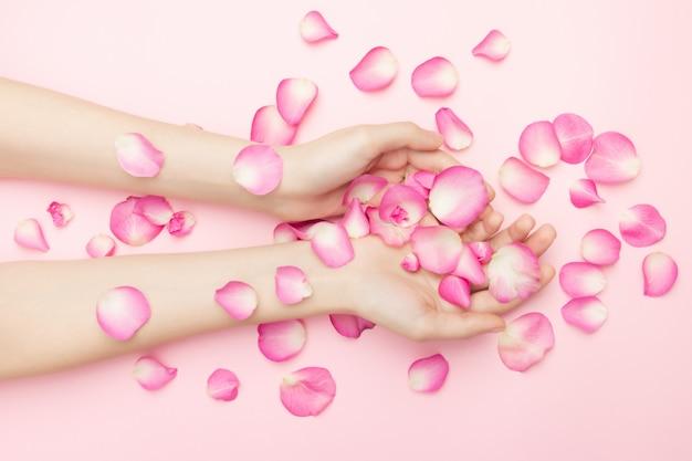 As mãos de mulher segurar flores rosas em uma superfície rosa. um pulso fino e manicure natural. cosméticos para cuidados com a pele sensíveis. cosméticos de pétalas naturais, cuidados com as mãos anti-rugas. Foto Premium