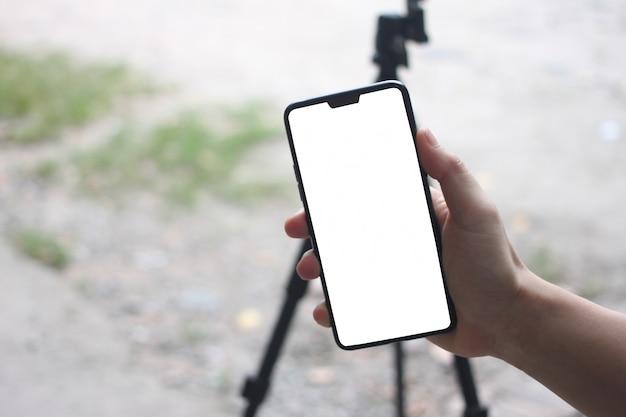 As mãos de um homem de negócios que guardam um smartphone vazio e têm o espaço da cópia. Foto Premium
