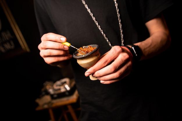 As mãos de um homem vestindo uma camiseta preta entopem uma tigela de narguilé com tabaco Foto Premium