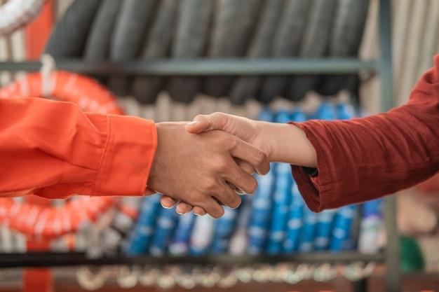 As mãos de um mecânico em um uniforme do wearpack apertam a mão de uma cliente contra um suporte de pneus Foto Premium