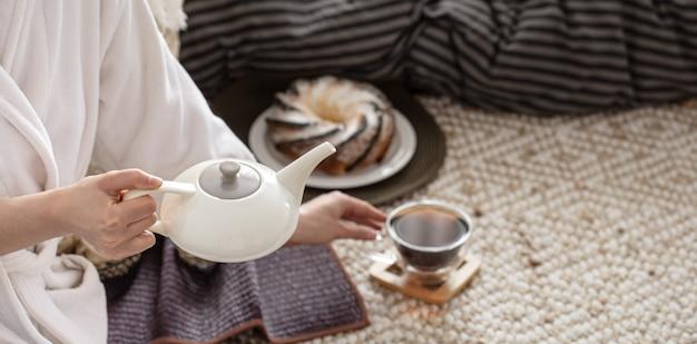 As mãos de uma jovem despejam o chá de um bule. Foto gratuita