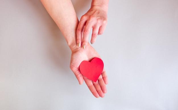 As mãos de uma senhora segurando um coração sobre a superfície, Foto Premium