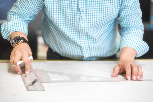 As mãos do alfaiate marcam o desenho no papel do ofício para fazer testes padrões. Foto Premium