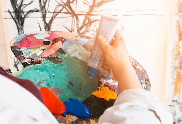 As mãos do artista espremem a tinta do tubo na paleta Foto gratuita