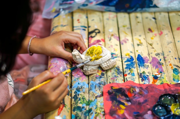 As mãos do close up dos estudantes de arte que guardam a escova de pintura estudam e que aprendem a pintura na boneca animal de madeira na sala de aula de arte. Foto Premium