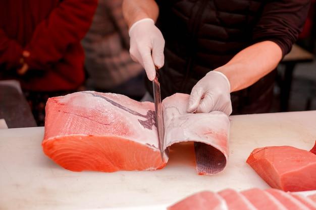 As mãos do cozinheiro chefe japonês que usam a faca do cozinheiro chefe cortaram a parte de peixes de atum frescos para a venda ao cliente no mercado de peixes da manhã, japão. Foto Premium