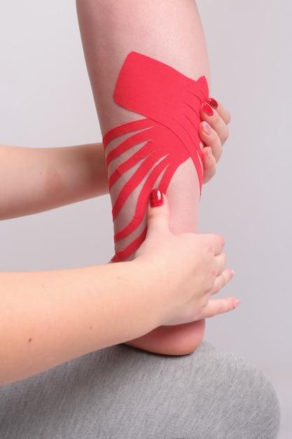 As mãos do fisioterapeuta que aplicam a fita do kinesio no pé da mulher fecham-se acima. visão vertical Foto Premium