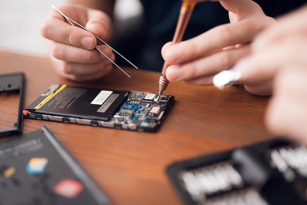 As mãos do homem desmontam o telefone com chave de fenda. Foto Premium