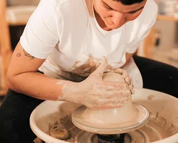 As mãos do homem fazendo pote de cerâmica na roda de oleiro Foto gratuita