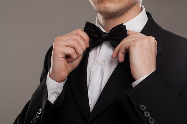 As mãos do homem tocam gravata borboleta Foto gratuita