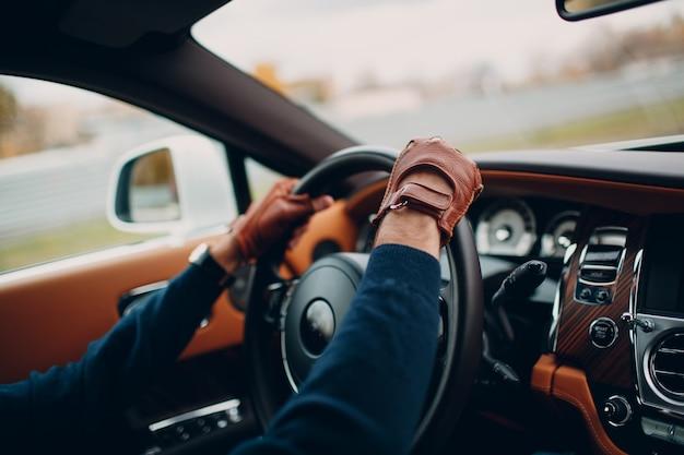 As mãos do motorista em luvas de couro, dirigindo um carro em movimento Foto Premium