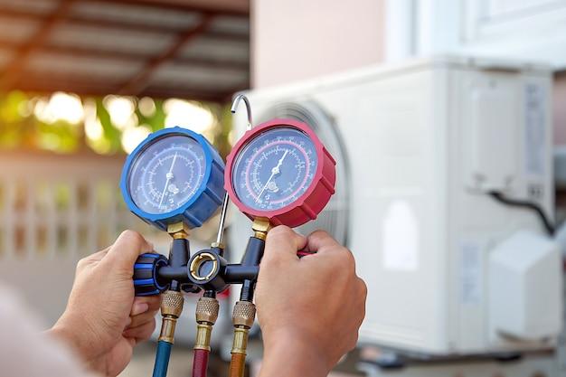 As mãos do técnico estão usando uma ferramenta de medição para verificar se a bomba de vácuo evacua o ar do condicionador de ar. Foto Premium