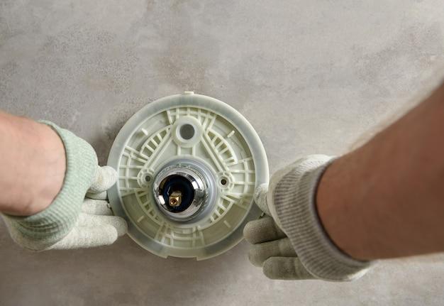 As mãos do trabalhador estão montando uma torneira embutida Foto Premium