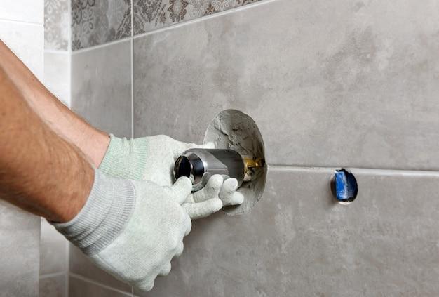 As mãos do trabalhador estão montando uma torneira embutida. Foto Premium