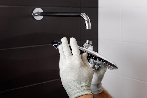 As mãos do trabalhador instalam a cabeça da torneira do chuveiro embutida Foto Premium
