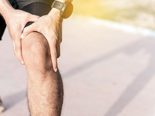 As mãos do uso do homem prendem em seu joelho ao correr na estrada no parque. Foto Premium