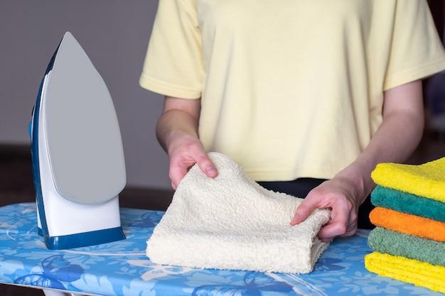As mãos dobram uma toalha passada, um ferro moderno com sistema de passar a vapor Foto Premium