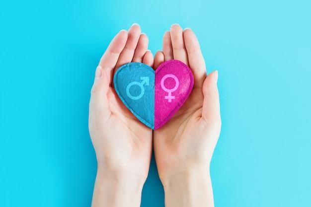 As mãos fêmeas guardam um coração com um símbolo masculino e fêmea em um fundo azul, copiam o espaço. menina ou menino, conceito de gravidez. conceito de gêmeos de gravidez Foto Premium