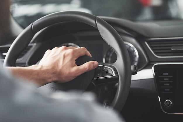 As mãos grandes do homem no volante enquanto dirige um carro. Foto gratuita