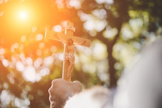 As mãos masculinas segurando jesus de madeira atravessam o céu com o fundo da natureza. Foto gratuita