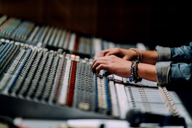 As mãos profissionais nas proximidades da mesa de som estão misturando sons pelo painel de controle do mixer de áudio. Foto Premium
