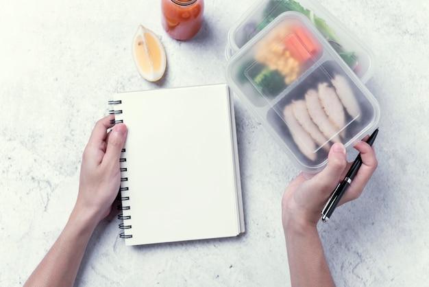 As mãos que guardam a lancheira saudável e o caderno vazio para sua mensagem ou projeto de texto, pedem o alimento. Foto Premium