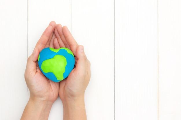 As mãos que guardam o coração global dão forma sobre o fundo de madeira branco com o espaço da cópia. Foto Premium