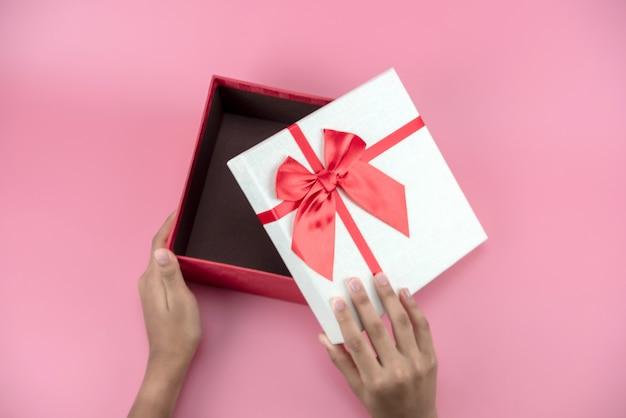 As mãos segura uma caixa de presente vermelha e branca vazia Foto Premium