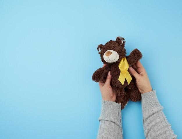 As mãos seguram um pequeno ursinho marrom que segura na pata uma fita amarela Foto Premium