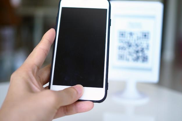 As mãos usam o telefone para escanear códigos qr para receber descontos nas compras. Foto Premium