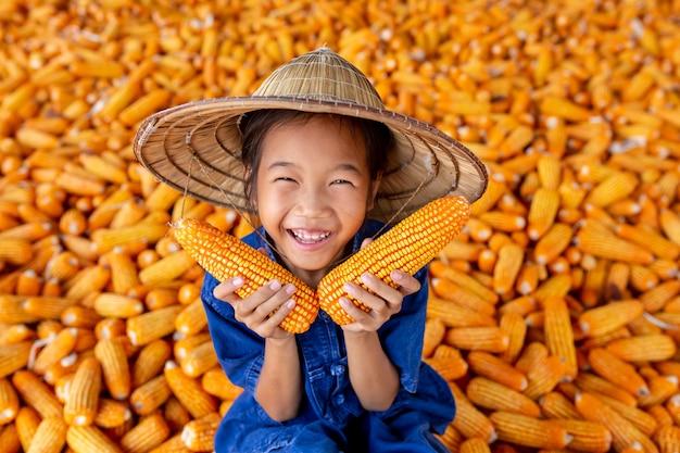 As meninas asiáticas prendem o milho entre o milho para o alimento. Foto Premium
