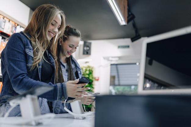 As meninas atrativas novas na eletrônica compram telefones de teste em uma vitrine. conceito de compra de gadgets. Foto gratuita