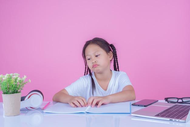 As meninas escrevem livros sobre um fundo rosa. Foto gratuita