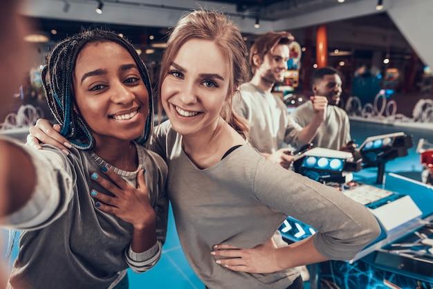 As meninas estão tomando selfie na sala de jogos. Foto Premium