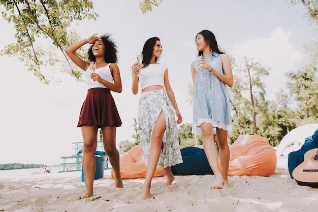 As meninas felizes bebem o acampamento do partido da praia de champagne. Foto Premium