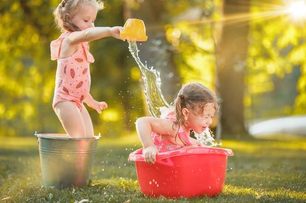 As meninas loiras bonitinha brincando com salpicos de água no campo no verão Foto gratuita