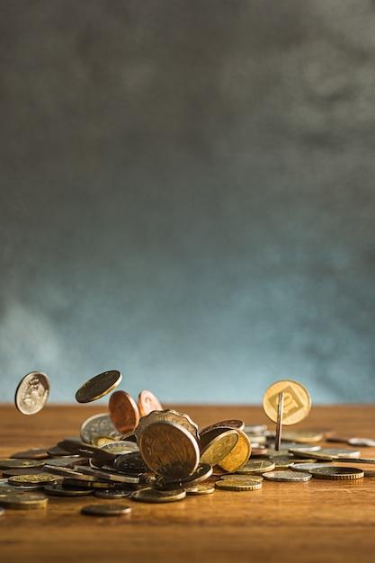 As moedas de prata e ouro e moedas caindo na mesa de madeira Foto gratuita