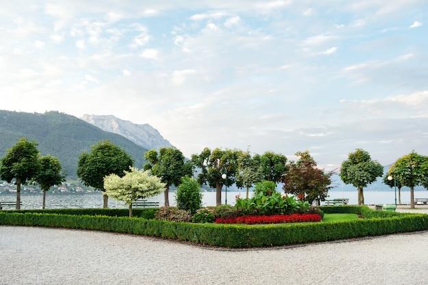 As montanhas, o lago e o aterro da cidade com árvores aparadas, arbustos e canteiros de flores. Foto Premium