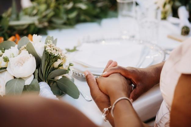 As mulheres afro-americanas seguram as mãos juntas na mesa de jantar Foto gratuita
