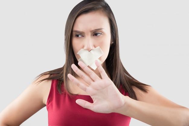 As mulheres asiáticas em vestidos vermelhos usam fita adesiva para fechar a boca Foto Premium