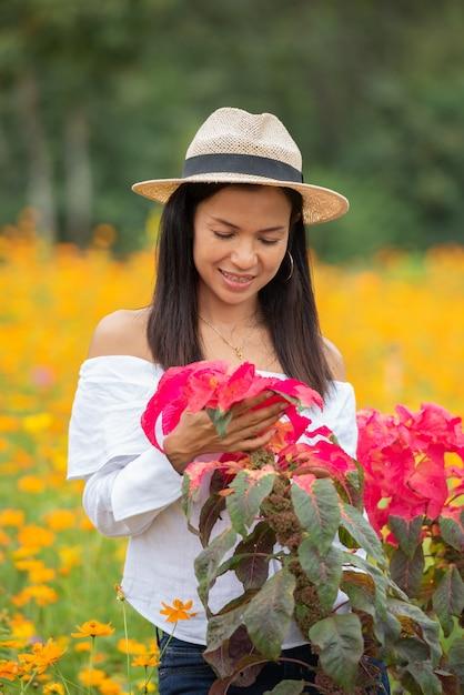 As mulheres asiáticas estão apreciando flores vermelhas no parque. Foto gratuita