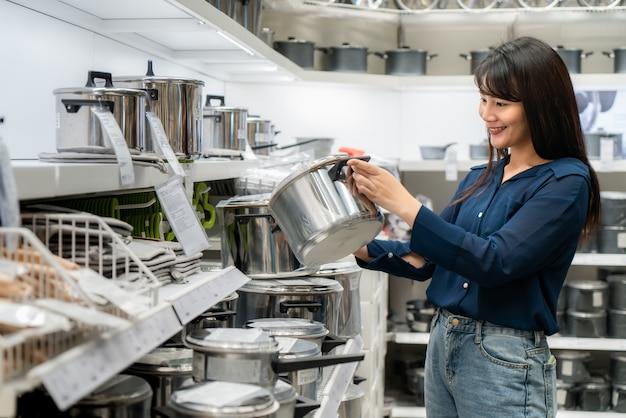 As mulheres asiáticas estão optando por comprar novos utensílios de cozinha no shopping Foto Premium
