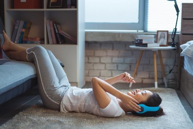 As mulheres asiáticas estão ouvindo música e ela canta no quarto feliz dormindo no tapete Foto Premium