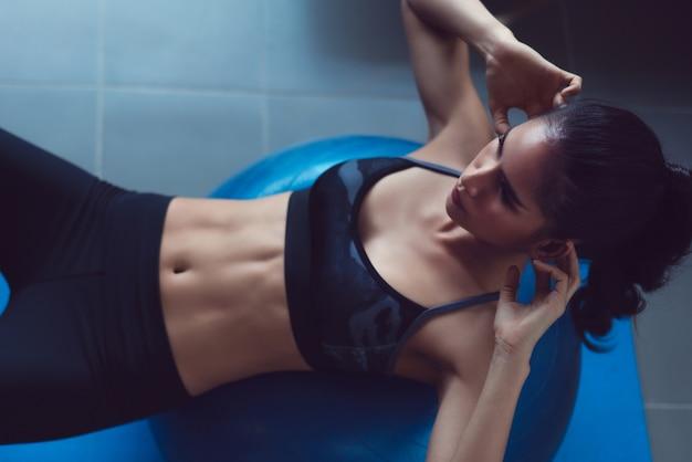 As mulheres asiáticas exercitam em casa.suas flexões na bola. Foto Premium