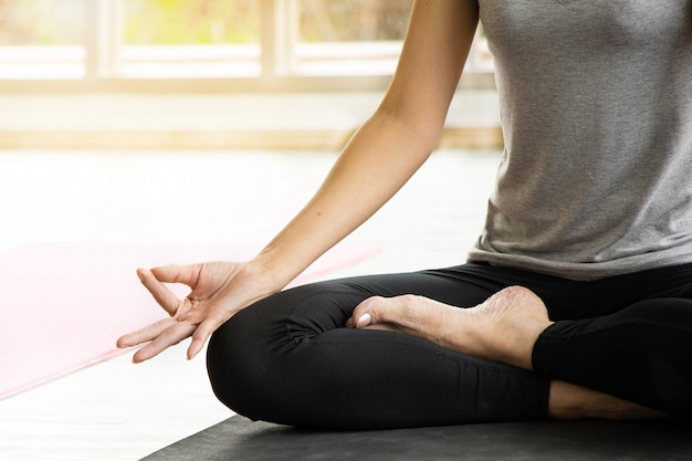 As mulheres asiáticas meditam enquanto praticam ioga, conceitos independentes, relaxando a felicidade das mulheres, a calma, o pano de fundo da sala branca. Foto Premium